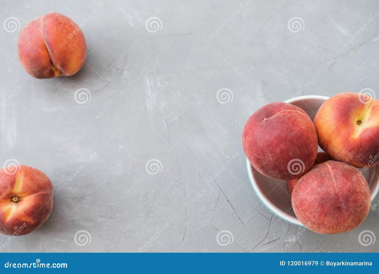 Reifer organischer Pfirsich in der blauen keramischen Schüssel im grauen Hintergrund oberseite
