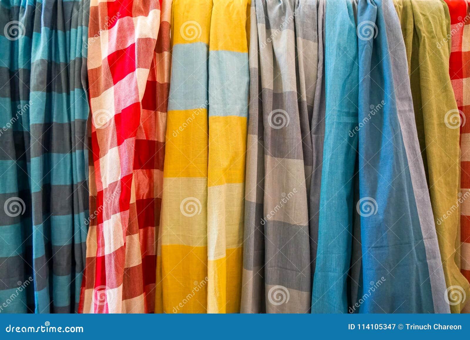Reihe von bunten weichen Baumwollgewebeschals in der Ebene und Kontrolleur kopieren den Verkauf im lokalen Shop