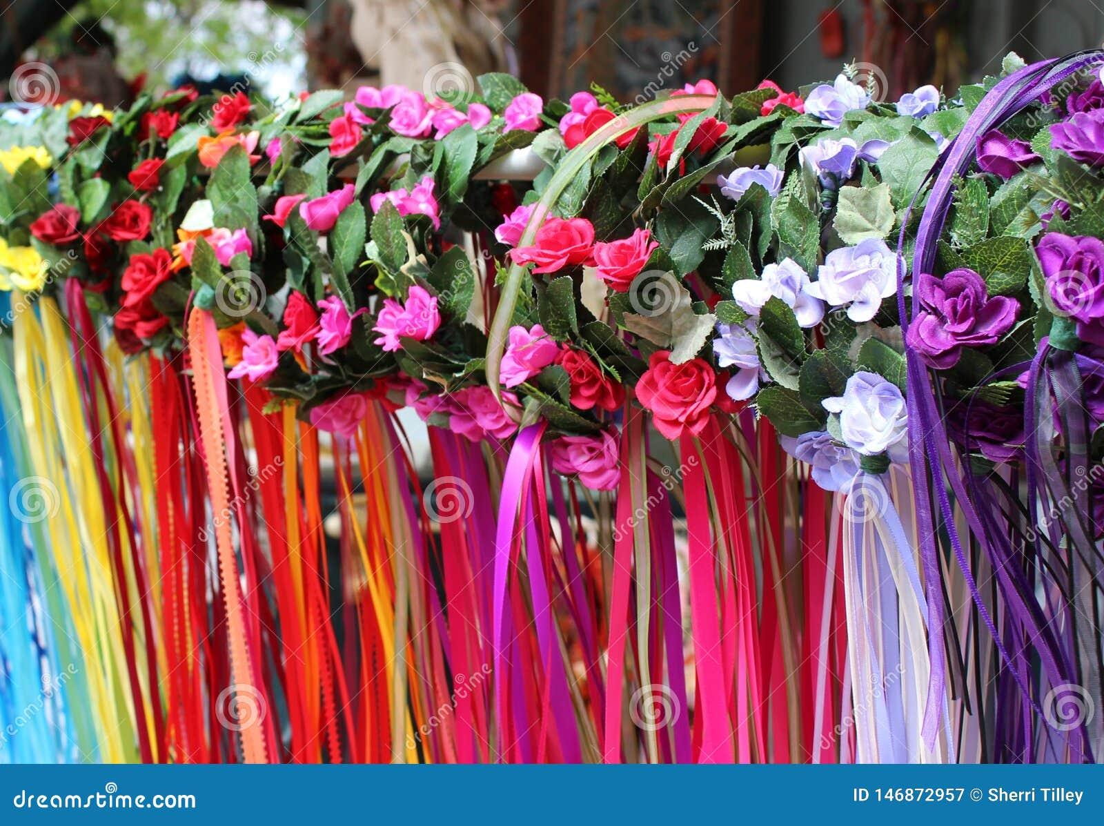 Reihen von Blume-bedeckten Mädchenstirnbändern mit bunten flüssigen Bandausläufern