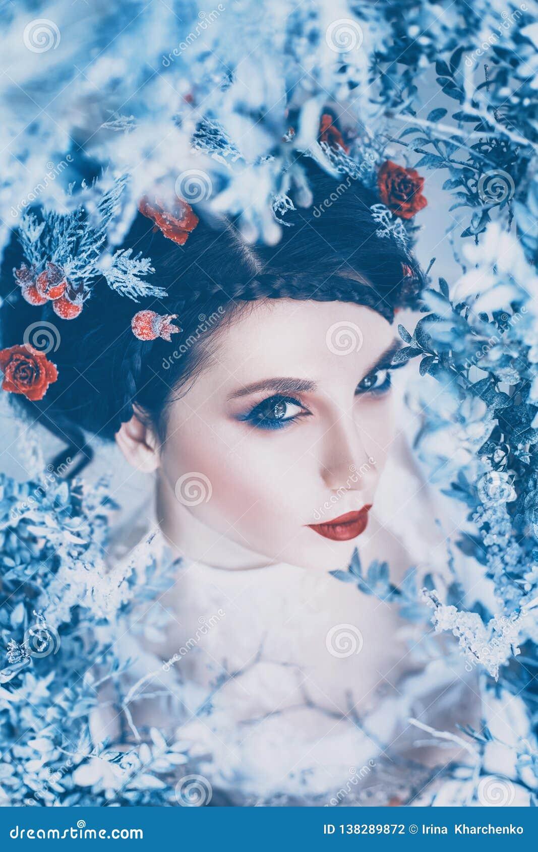 Reina majestuosa orgullosa del invierno y del frío eterno en vestido blanco largo con el pelo recogido oscuro adornado con las ro