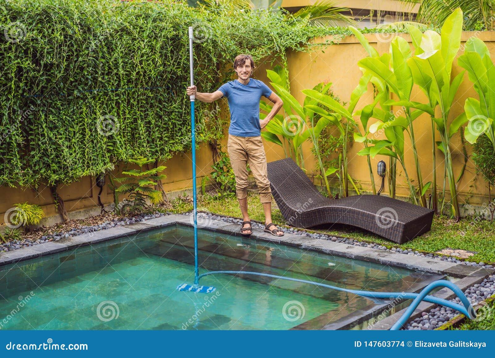 Reiniger des Swimmingpools Mann in einem blauen Hemd mit Reinigungsanlage f?r Schwimmb?der Poolreinigungsdienstleistungen