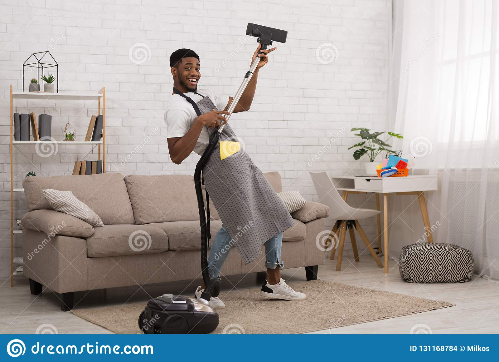 Reinigungshaus des jungen Mannes mit Staubsauger