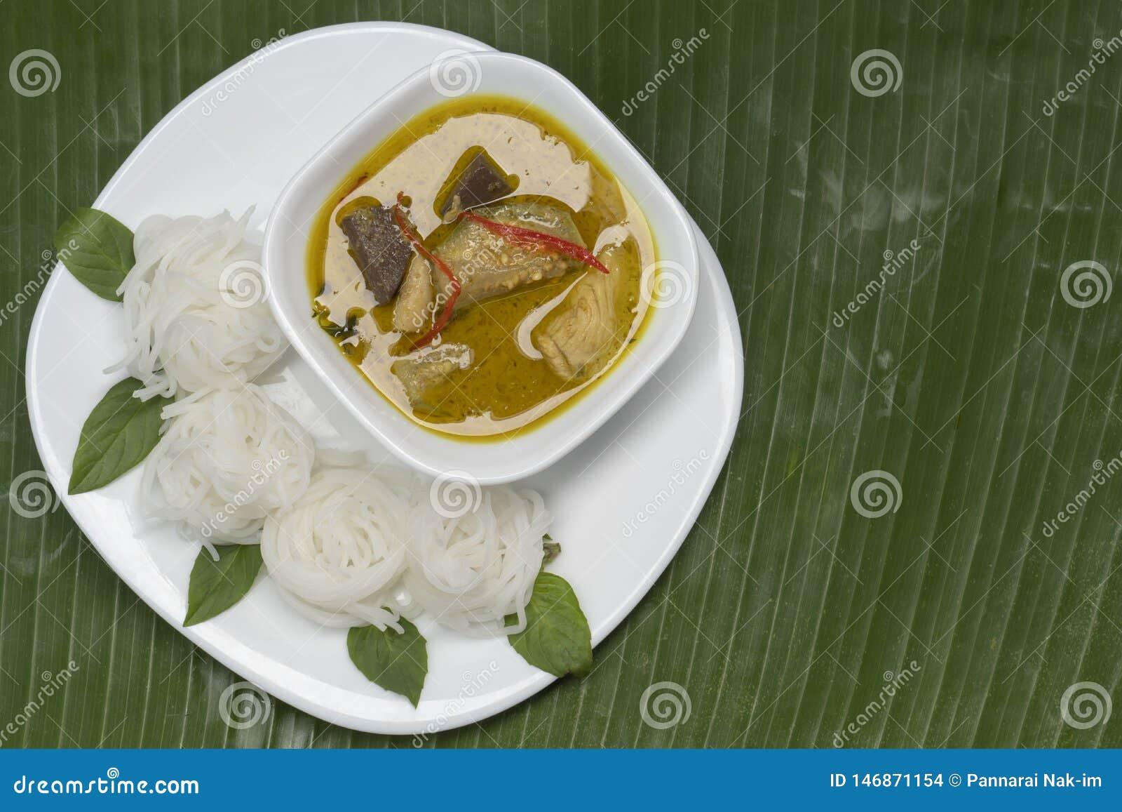 Reis-Suppennudeln mit grünem Curry-Huhn in der weißen Platte und in der Schüssel