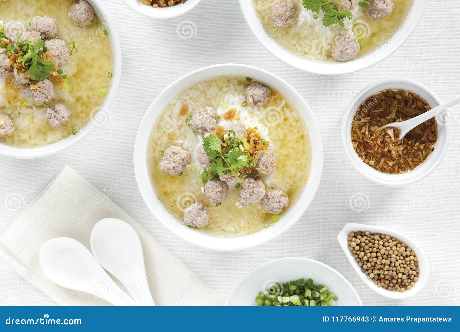 Reisbrei mit Schweinekoteletts und Gewürz in den weißen Schüsseln auf weißer Tabelle der Draufsicht, chinesisches Lebensmittel
