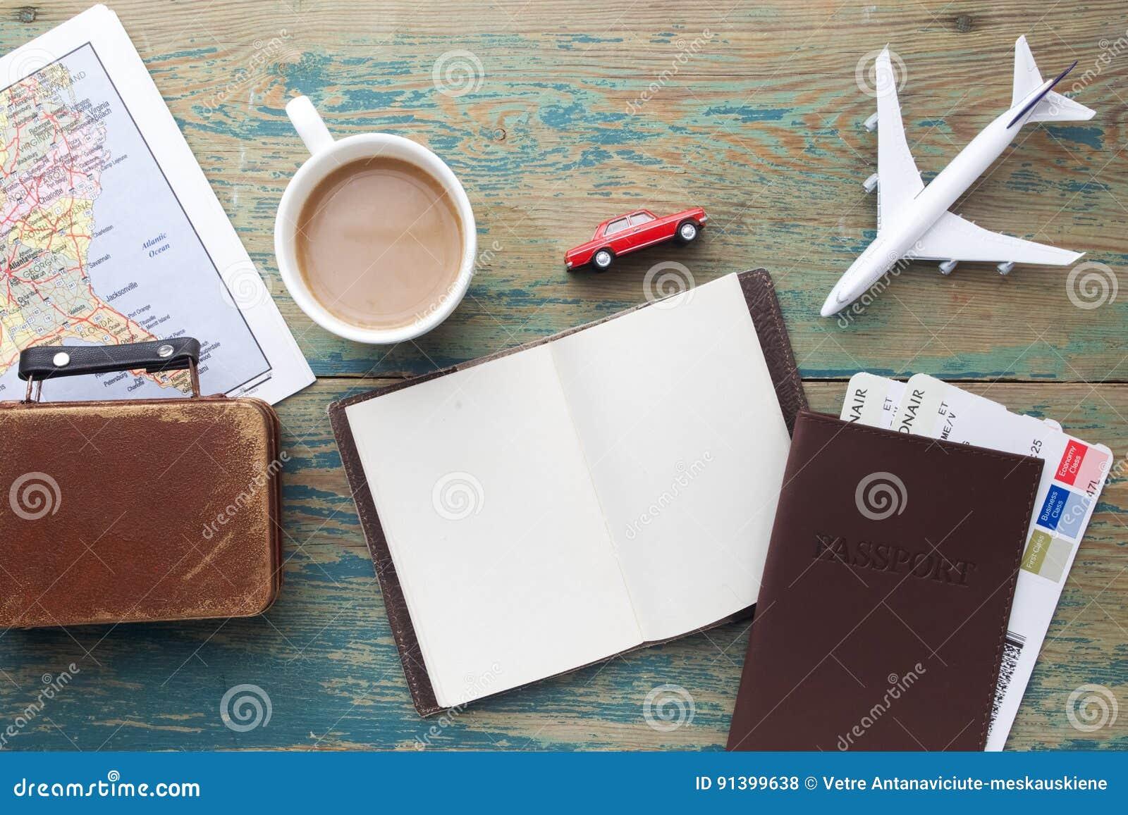 Reise, Reiseferien, Tourismusmodell - nahes hohes Anmerkungsbuch, Koffer, Spielzeugflugzeug und touristische Karte auf Holztisch