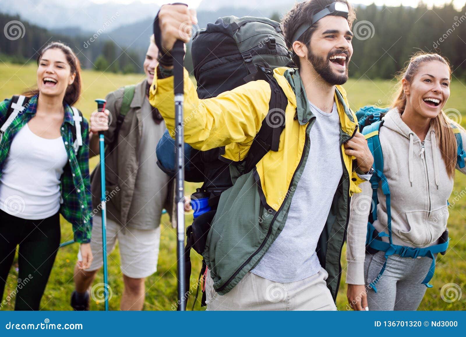 Reise-, Tourismus-, Wanderungs-, Gesten- und Leutekonzept - Gruppe lächelnde Freunde mit Rucksäcken