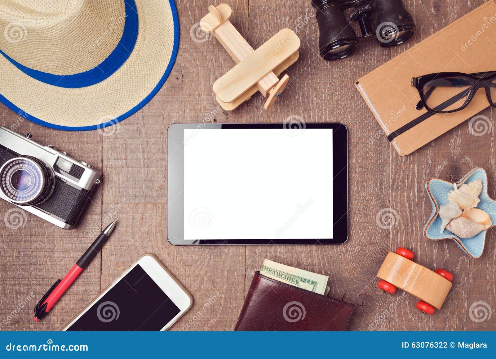 Reise- und Ferienkonzepthintergrund mit digitalem Tablettenspott oben und Gegenständen Ansicht von oben