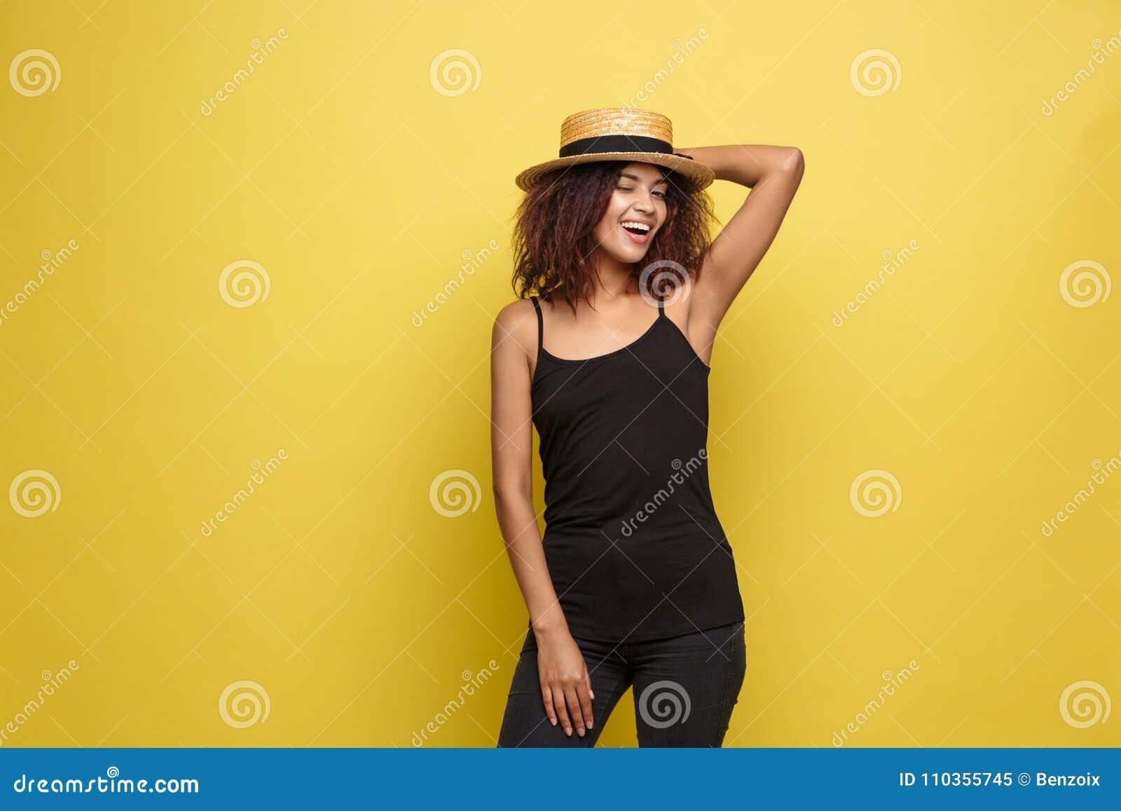 Reisekonzept - nahes hohes Porträt-junge schöne attraktive Afroamerikanerfrau mit modischem Hut lächelnd und froh