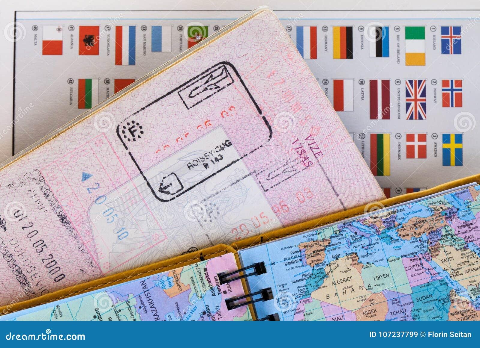 Reisekonzepthintergrund mit Karte, Pass mit Gewohnheitseinreisestempeln und bunte Staatsflaggen