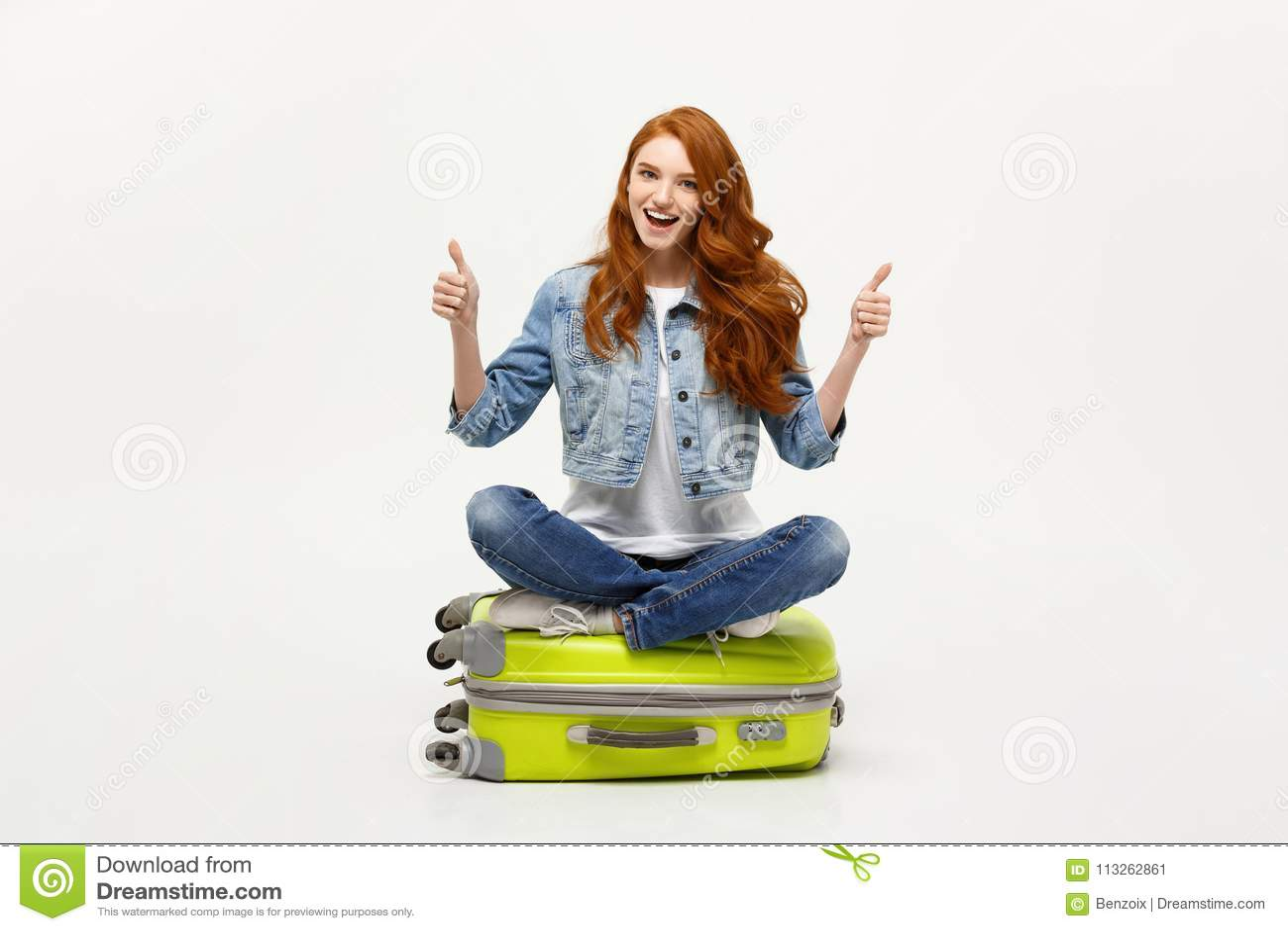 Reisen und Lebensstilkonzept Junge aufgeregte kaukasische Frau, die auf dem Gepäck valise sich zeigt Daumen sitzt Getrennt