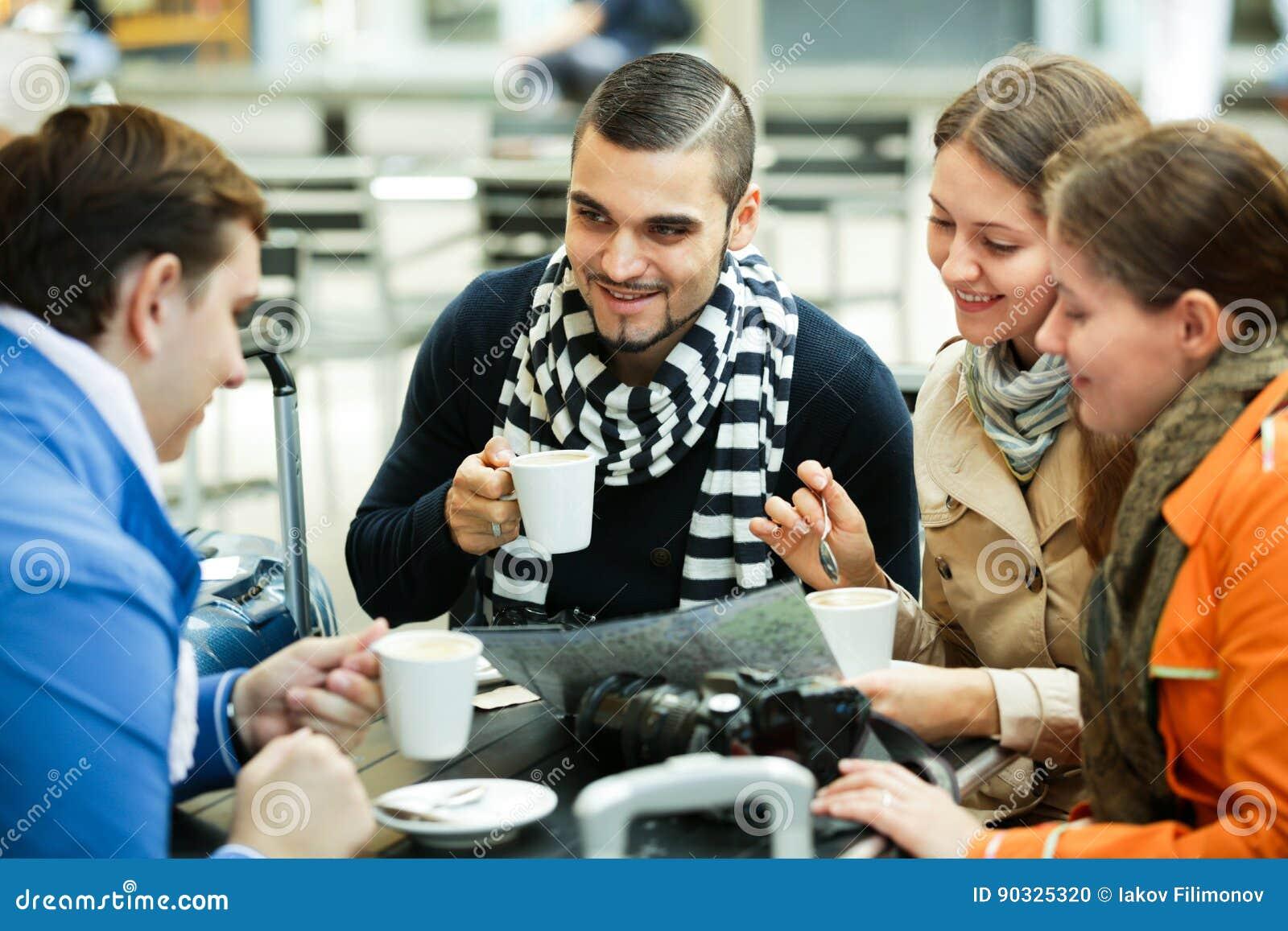 Reisende, die mit Karte im Café sitzen