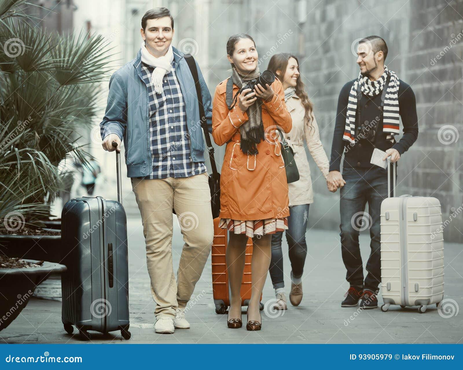 Reisende mit Gepäckbesichtigung und -c$lächeln im Herbst