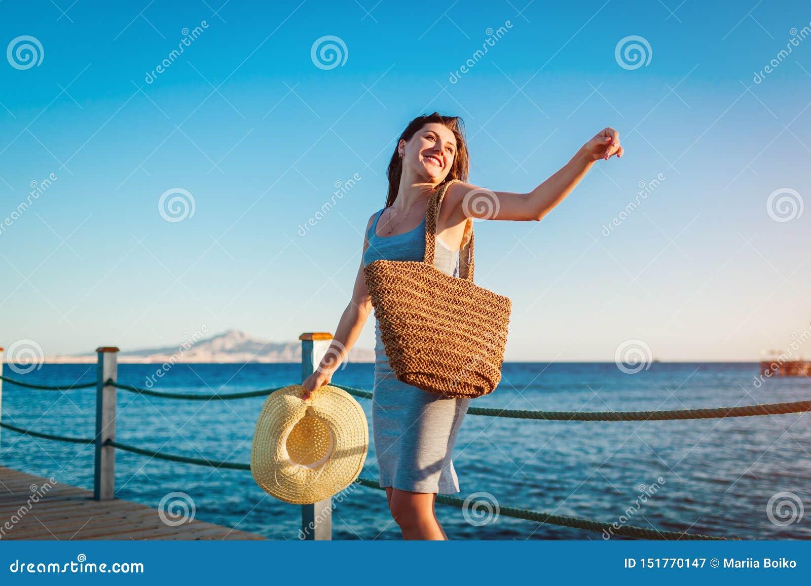 Reisender der jungen Frau ?ffnet Arme und das F?hlen gl?cklich und frei auf Pier durch Rotes Meer