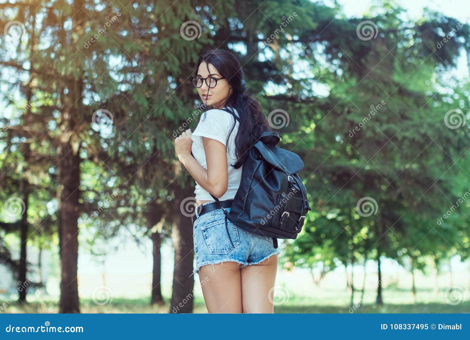 Reisender der jungen Frau mit dem Rucksack, der allein im Waldhippie-Mädchen im sonnigen Holz steht