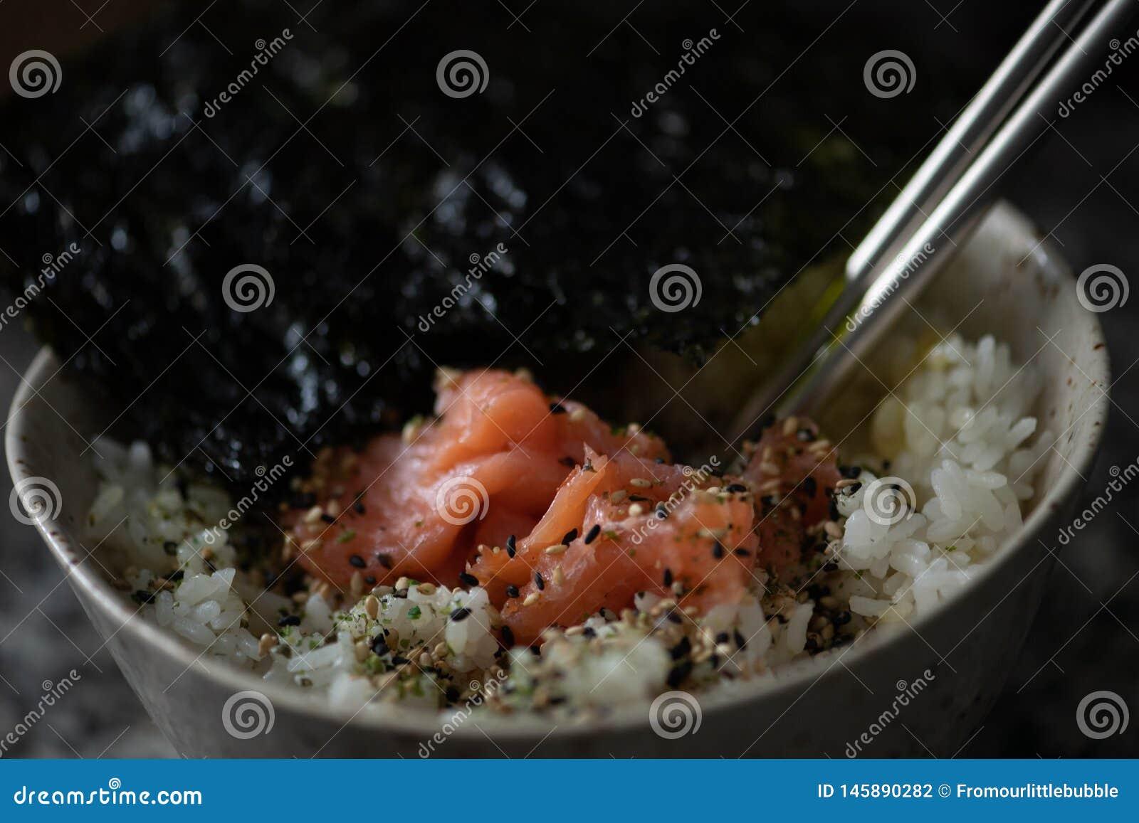 Reisschale mit Lachsen und Meerespflanze