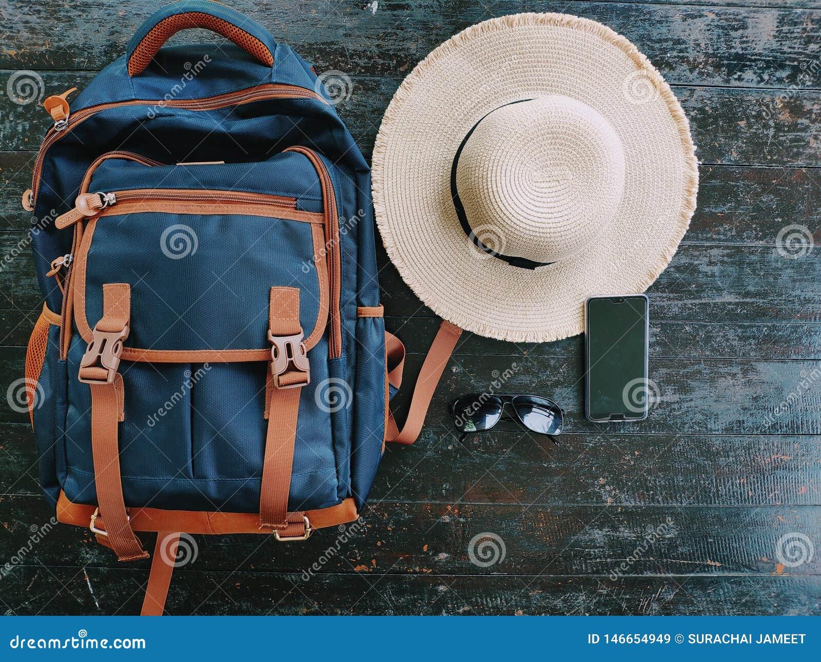 Reistas, hoed, zonglazen, mobiele telefoon, die op een houten lijst wordt geplaatst die op het reizen tijdens de aanstaande vakan