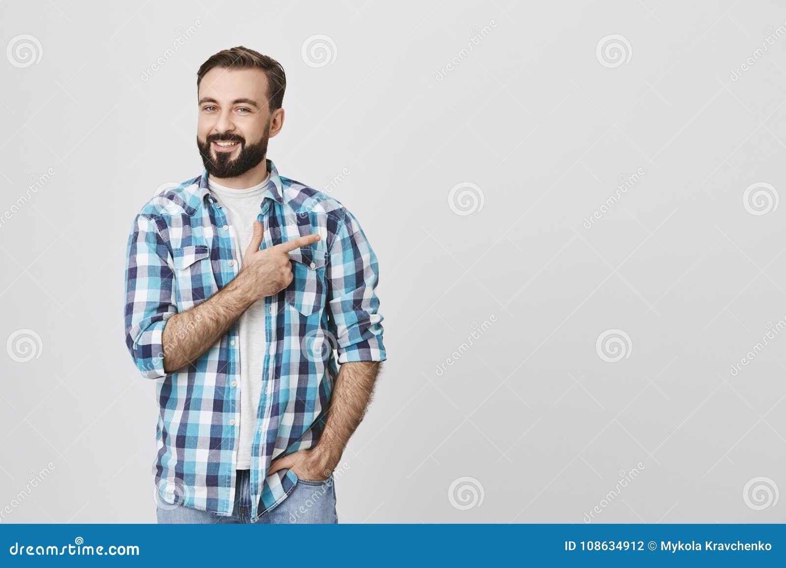 Reizend bärtiger erwachsener Mann im blauen karierten Hemd nach rechts zeigend mit dem Zeigefinger während eine andere Hand in de