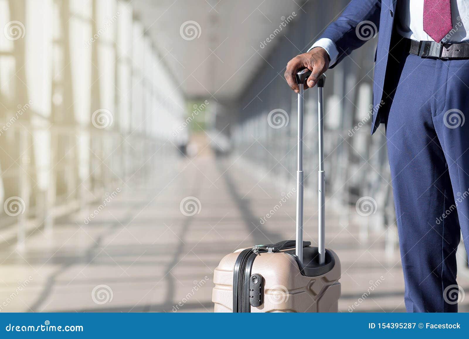 Reizend concept De Afrikaanse mens die zijn koffer in luchthaven houden, sluit omhoog