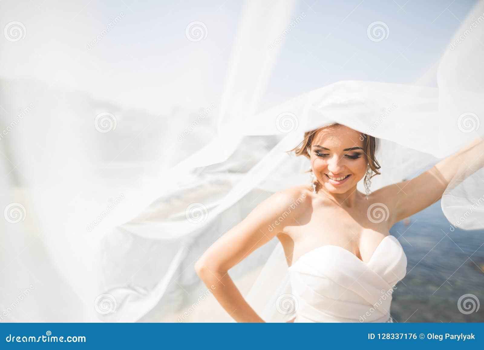 Reizende Braut im weißen Hochzeitskleid, das nahe dem Meer mit schönem Hintergrund aufwirft