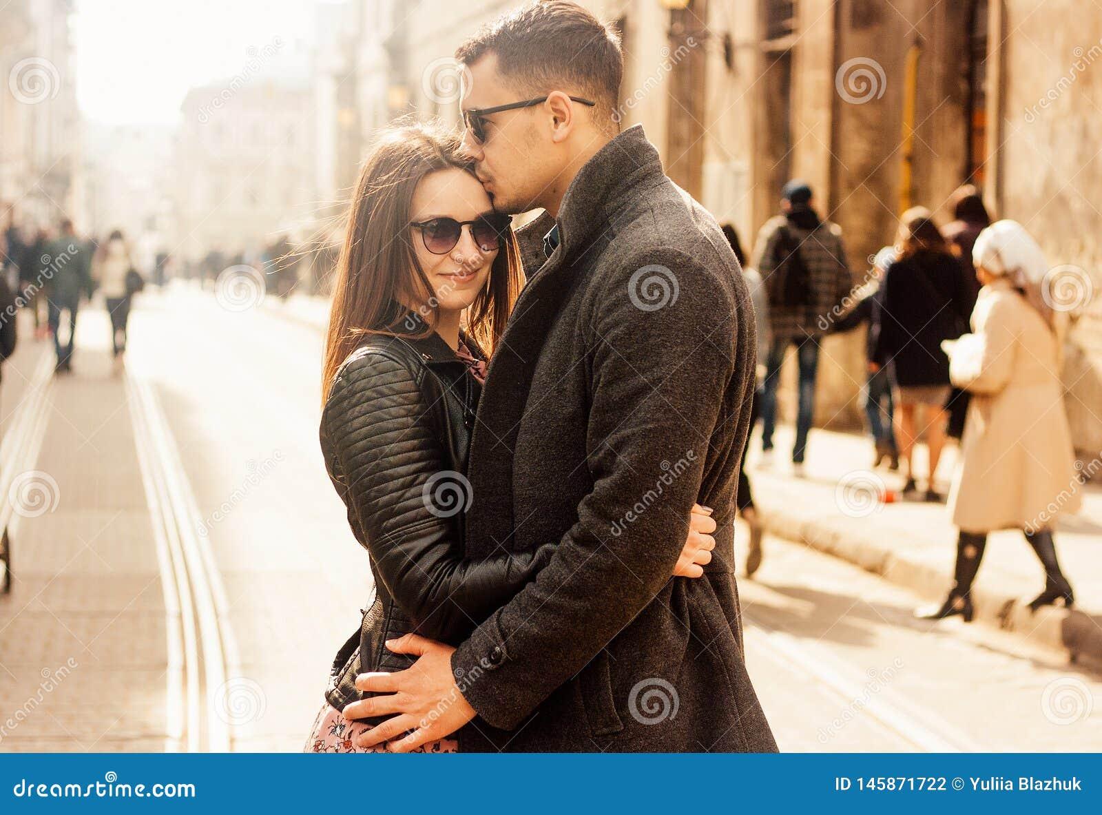 Reizende junge Paare, die an der Straße umarmen