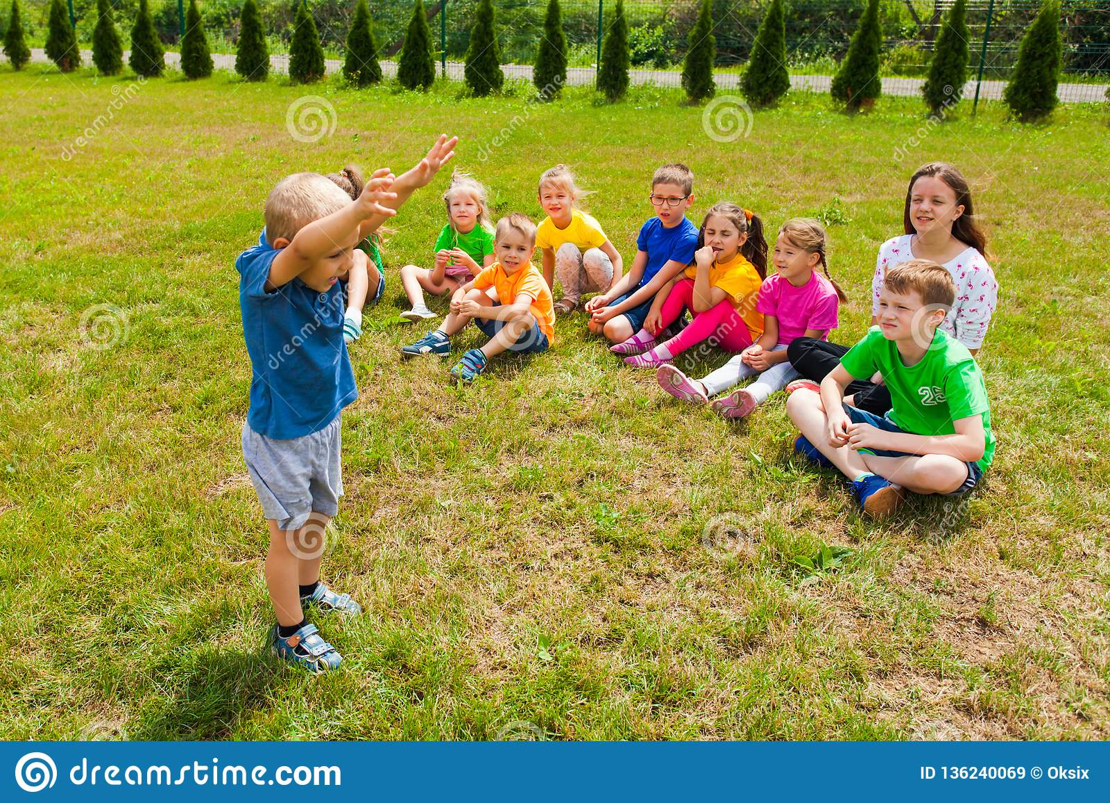 Reizende Jungenstellung vor Gruppe Kindern