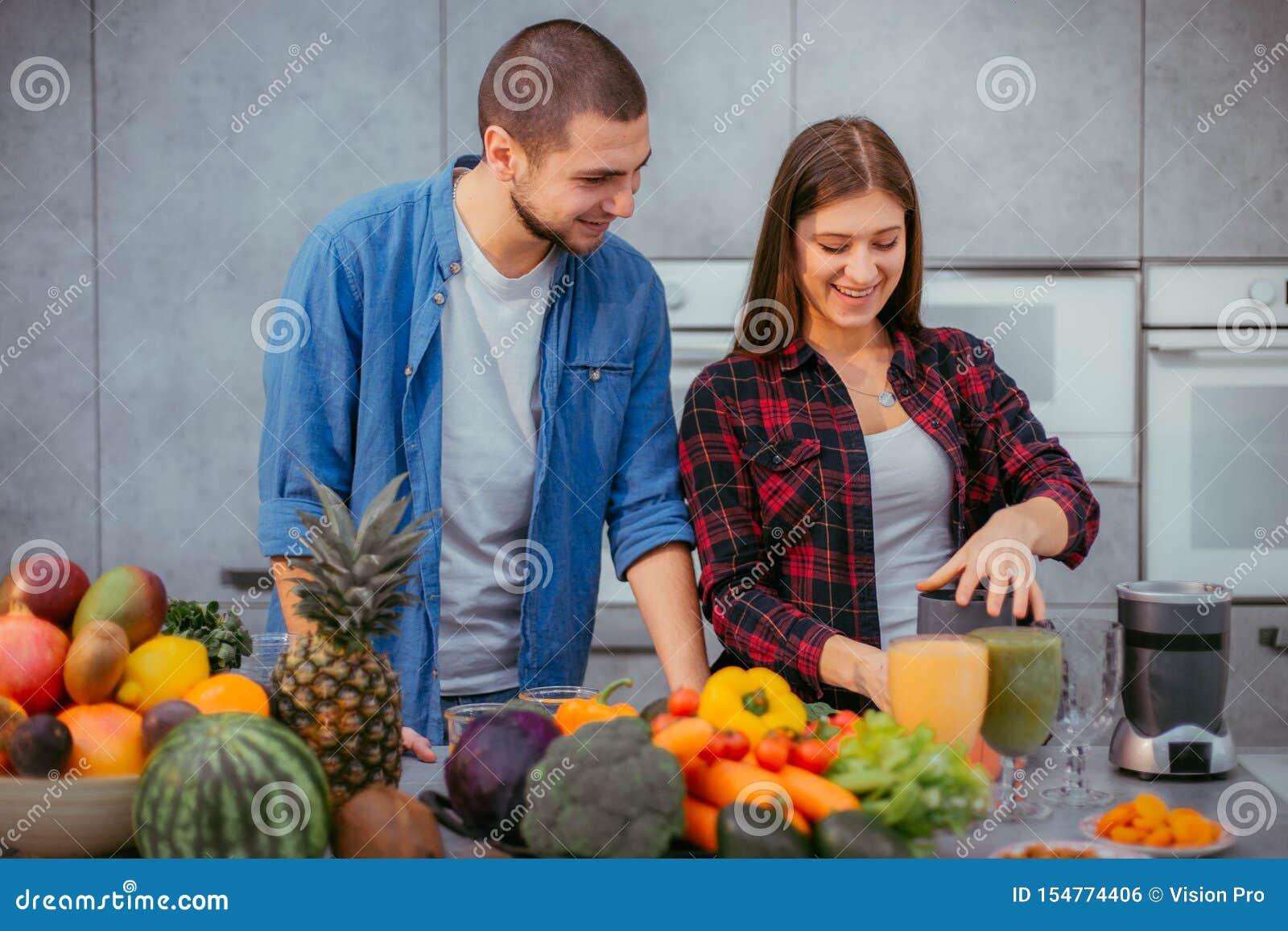 Reizende Paare haben morgens eine gute Laune, die gl?cklich ist, trinkt frischen Orangensaft, bevor sie das Fr?hst?ck kochen