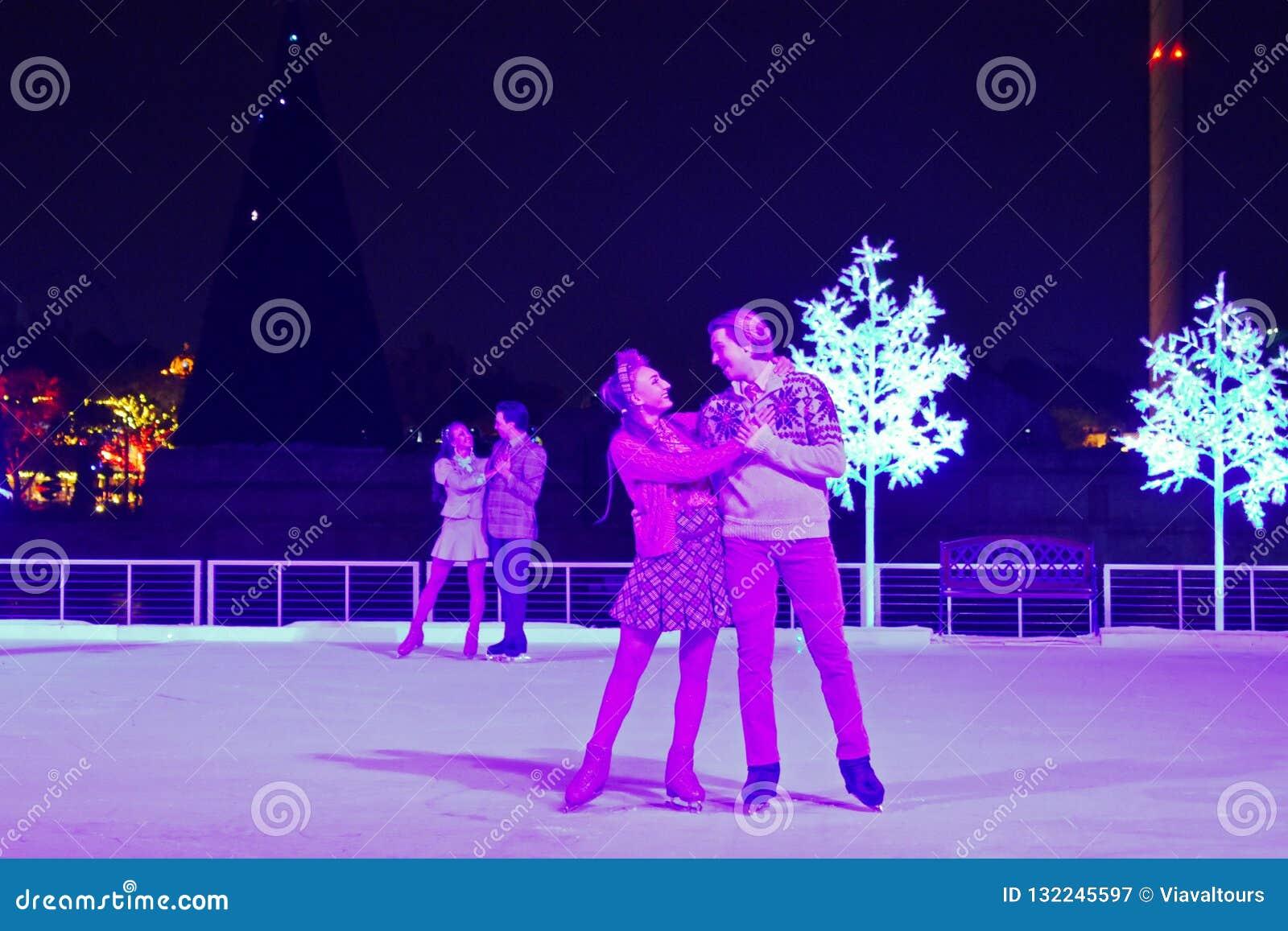Reizenden Paares, das auf Eis am Weihnachtszeigung im internationalen Antriebsbereich eisläuft