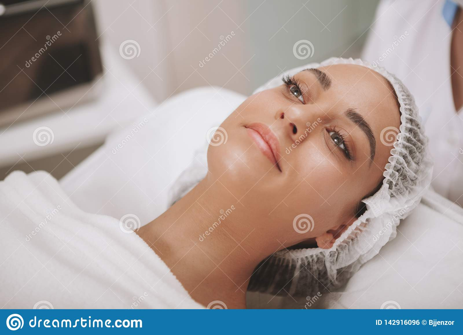 Reizender junge Frau Besuchscosmetologist an der Schönheitsklinik