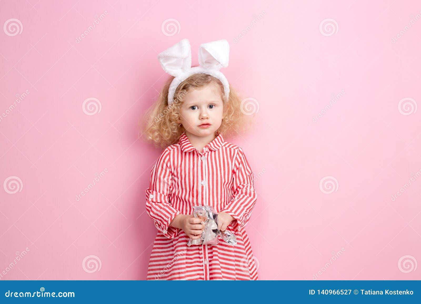 Reizendes kleines Mädchen in gestreiften roten und weißen Kleider- und Häschenohren auf ihrem Kopf steht gegen eine rosa Wand und