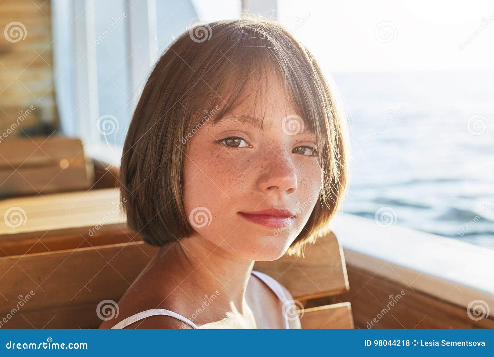 Reizendes Mädchen mit dunklen Augen und den Sommersprossen, gekleidet im Sommerkleid, Kamera beim Sitzen betrachtend an der Holzb