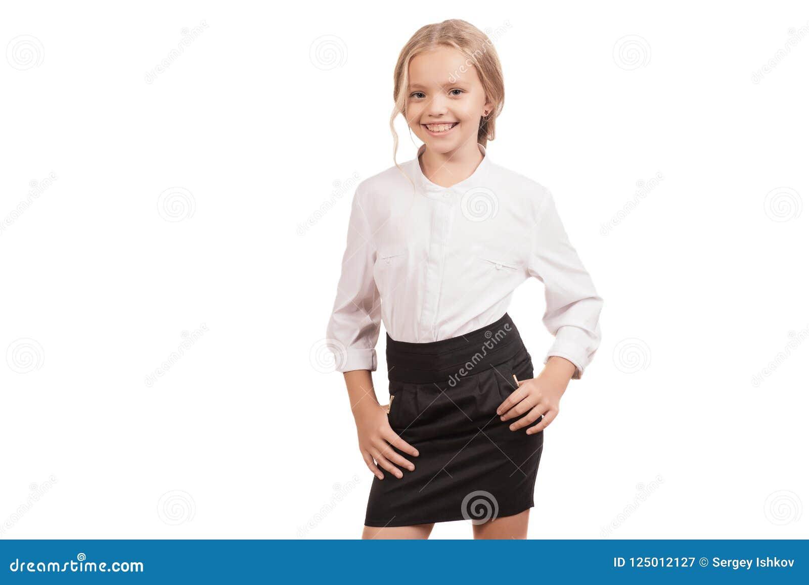Reizendes Schulmädchen mit neun Jährigen in einem Hemd und in einem Rock