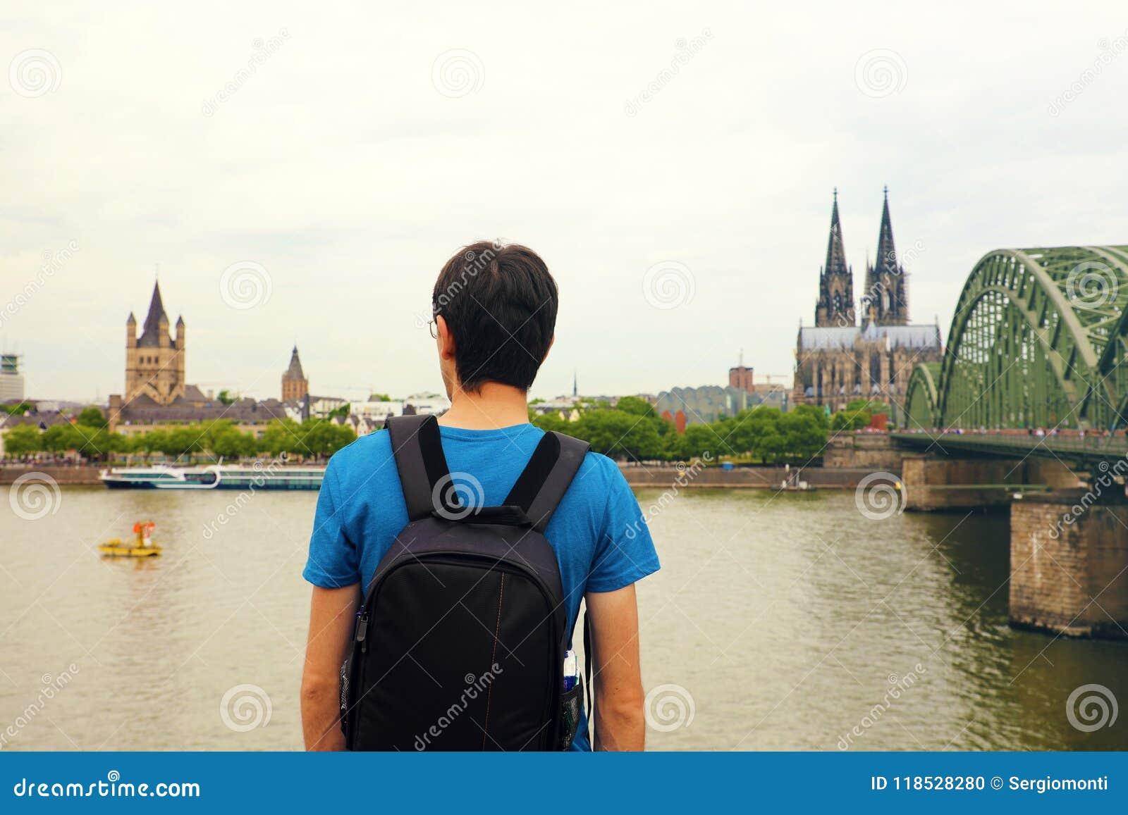 Reizigersmens die van zijn vakantie in Europa genieten Achtermening van mannetje die backpacker aan de Stad van Keulen met Kathed