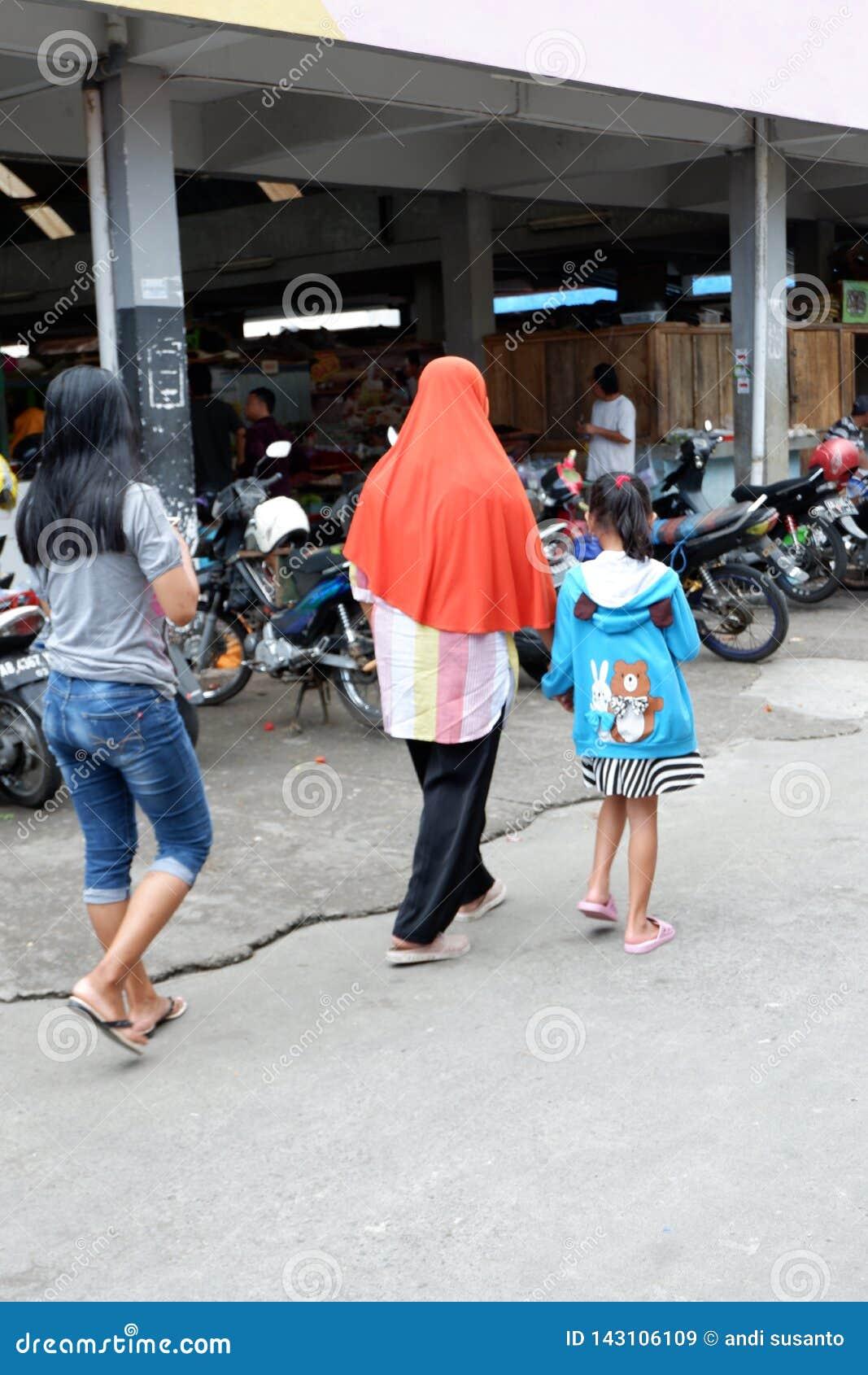 Rejowinangun,马格朗,印度尼西亚- 2019年3月24日:配比的母亲和孩子,当购物在传统市场上时
