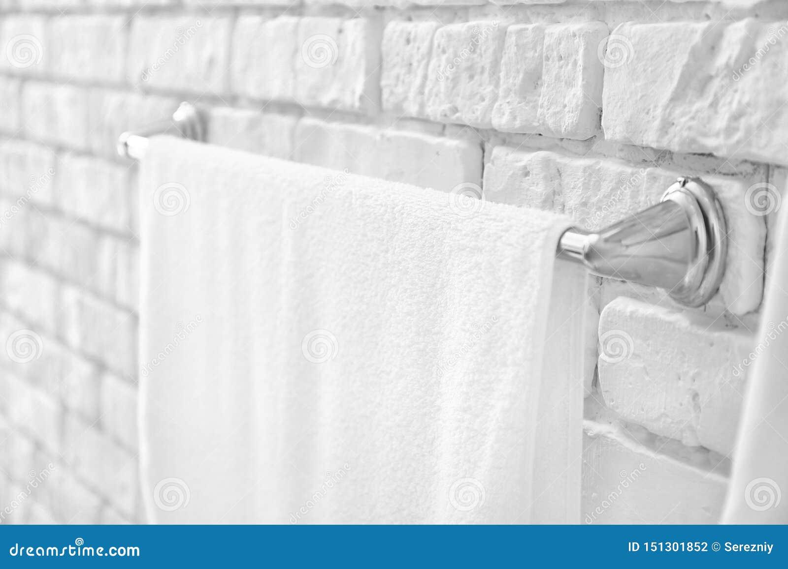 Rek met handdoek op bakstenen muur