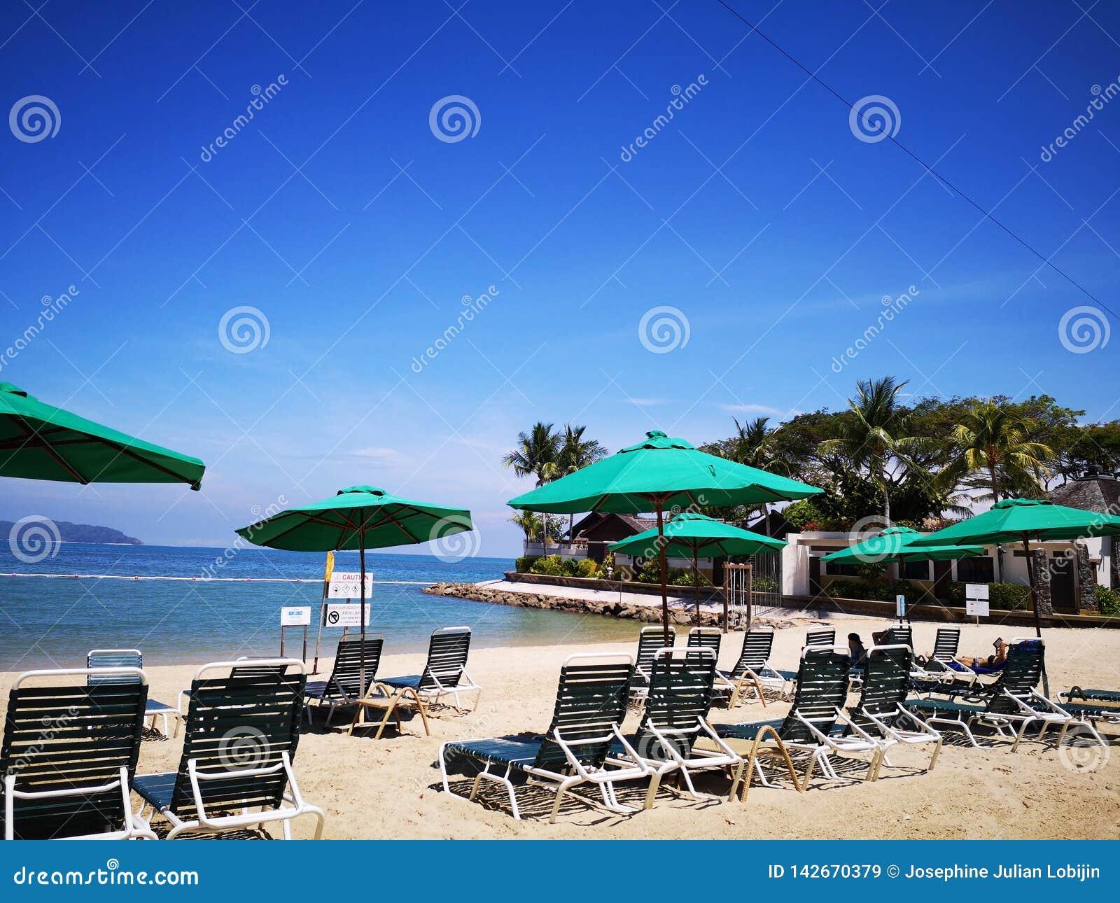 Relájese y goce en la playa con las sillas perezosas en la playa y el cielo azul hermoso arriba