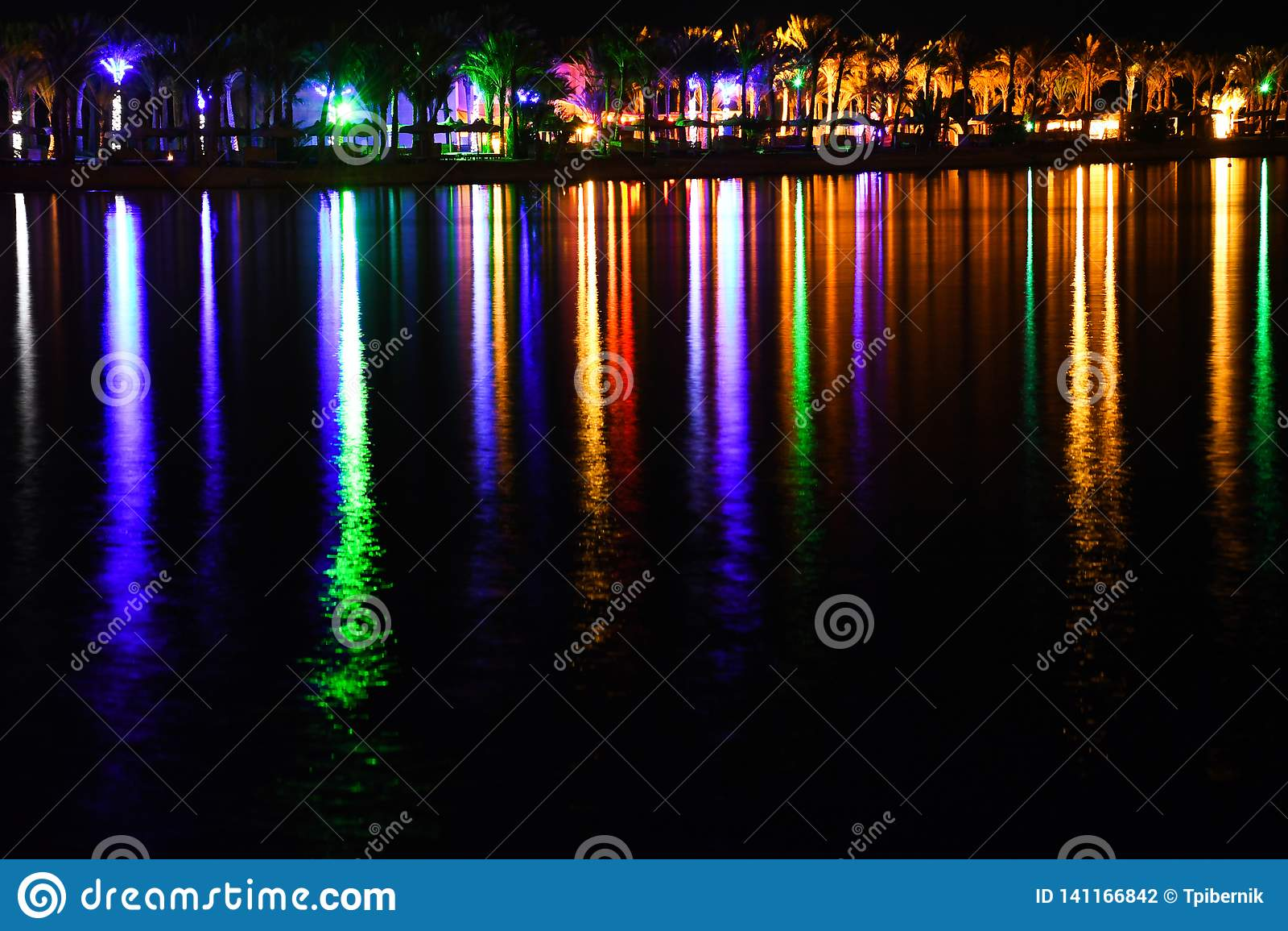 Relámpago de la noche y playa brillante con las luces coloridas y la reflexión larga hermosa