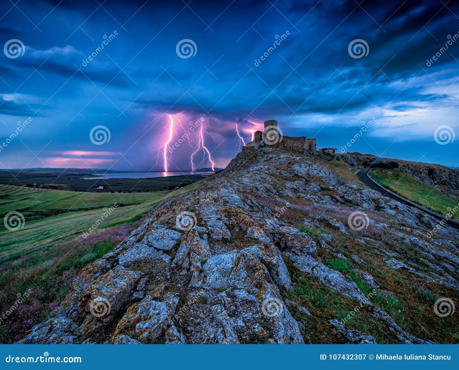 Relâmpago dos raios em um céu azul da noite nebulosa sobre a citadela velha da fortaleza de Enisala