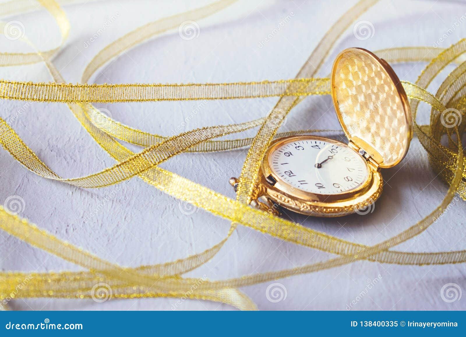 Relógio de bolso do vintage do ouro com as fitas douradas no fundo cinzento do cimento Temporizador da ampulheta ou da areia, sím