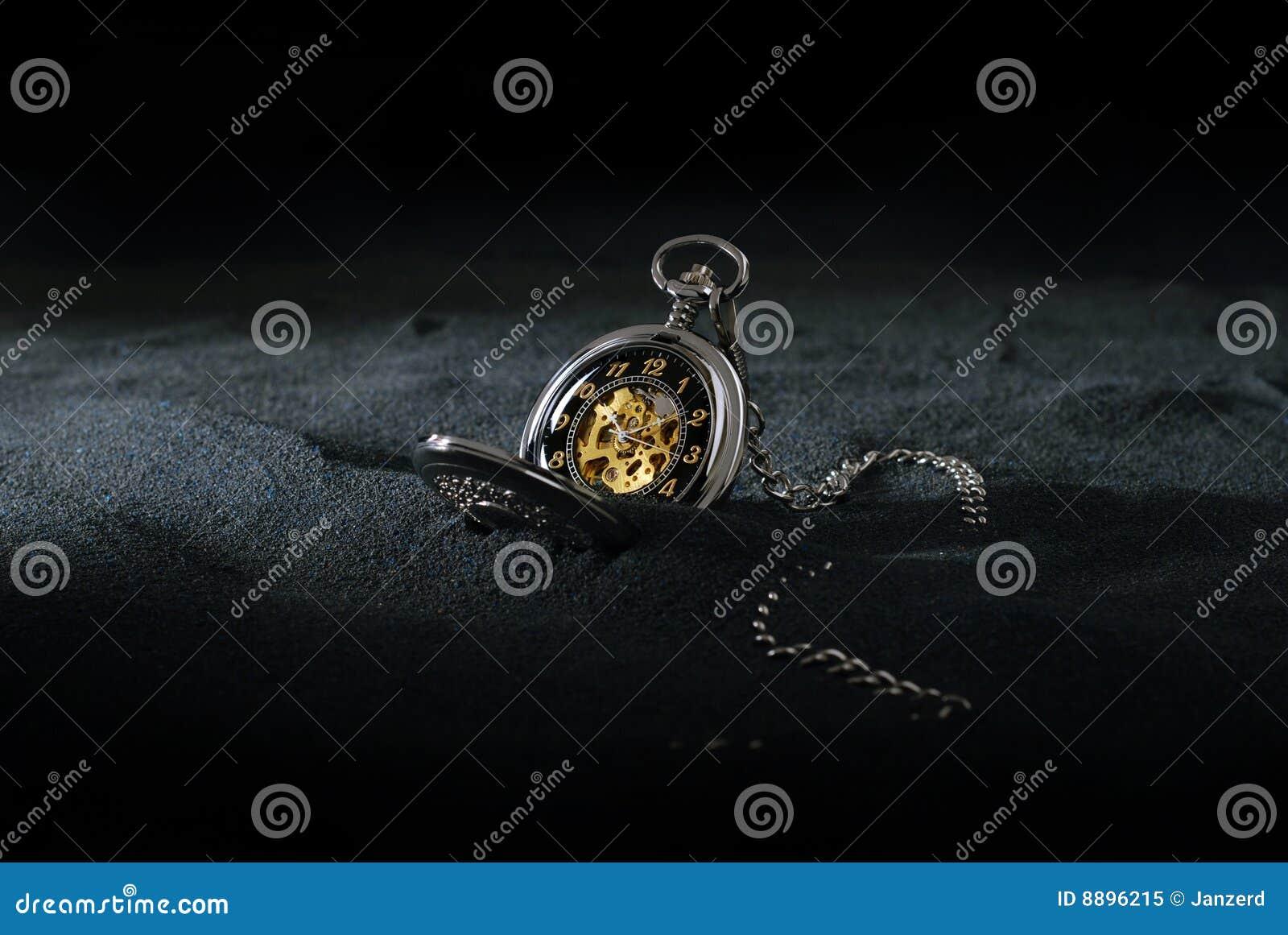 Relógio de bolso na areia