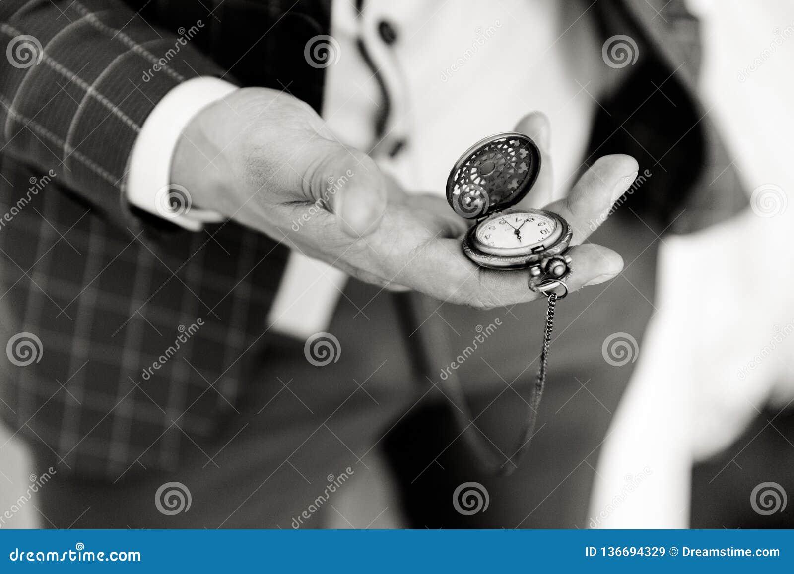 Relógio de bolso na mão de um homem