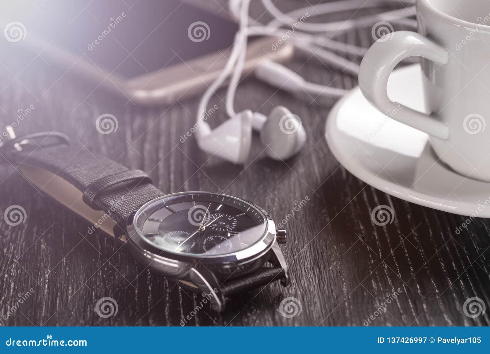 Relógio de pulso e telefone celular com fones de ouvido e uma xícara de café em uma tabela de madeira escura