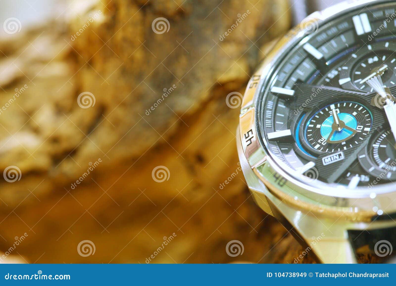 Relógio do cronógrafo posto ao lado do fundo de madeira