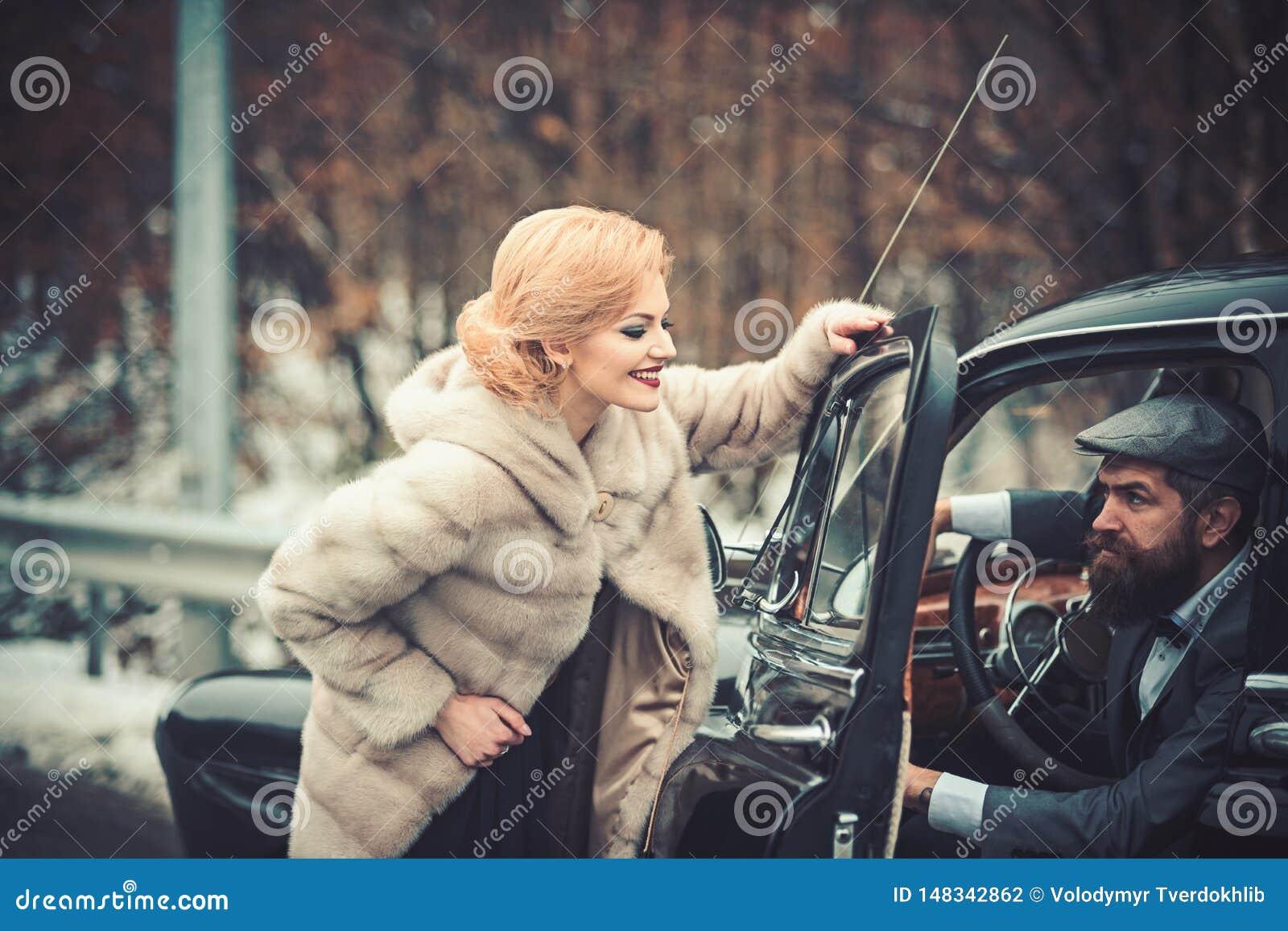 Relaci?n rom?ntica de la muchacha y del hombre atractivos pares rom?nticos en el coche retro