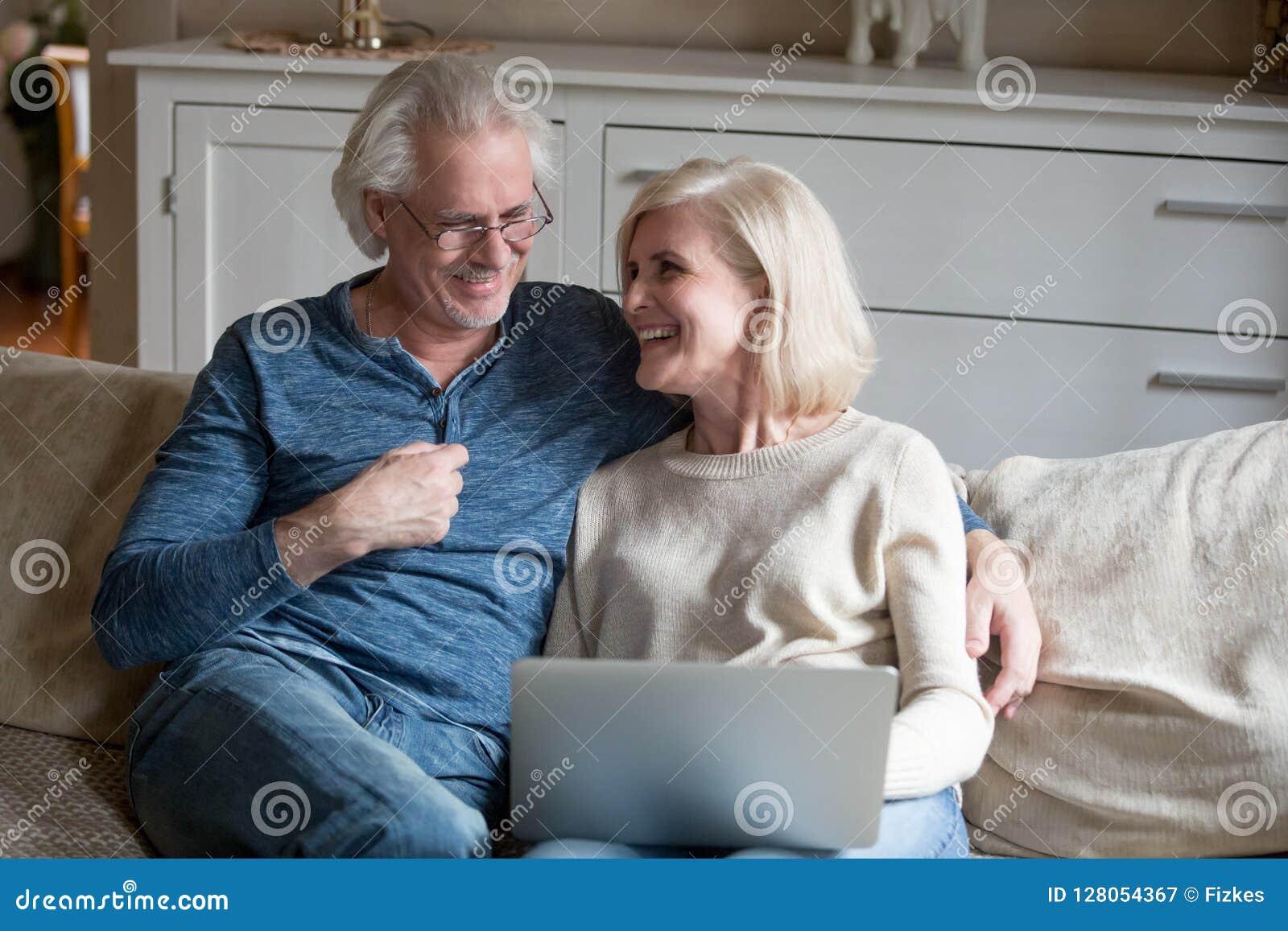 Relajación de risa de los pares mayores felices con el ordenador portátil en sala de estar