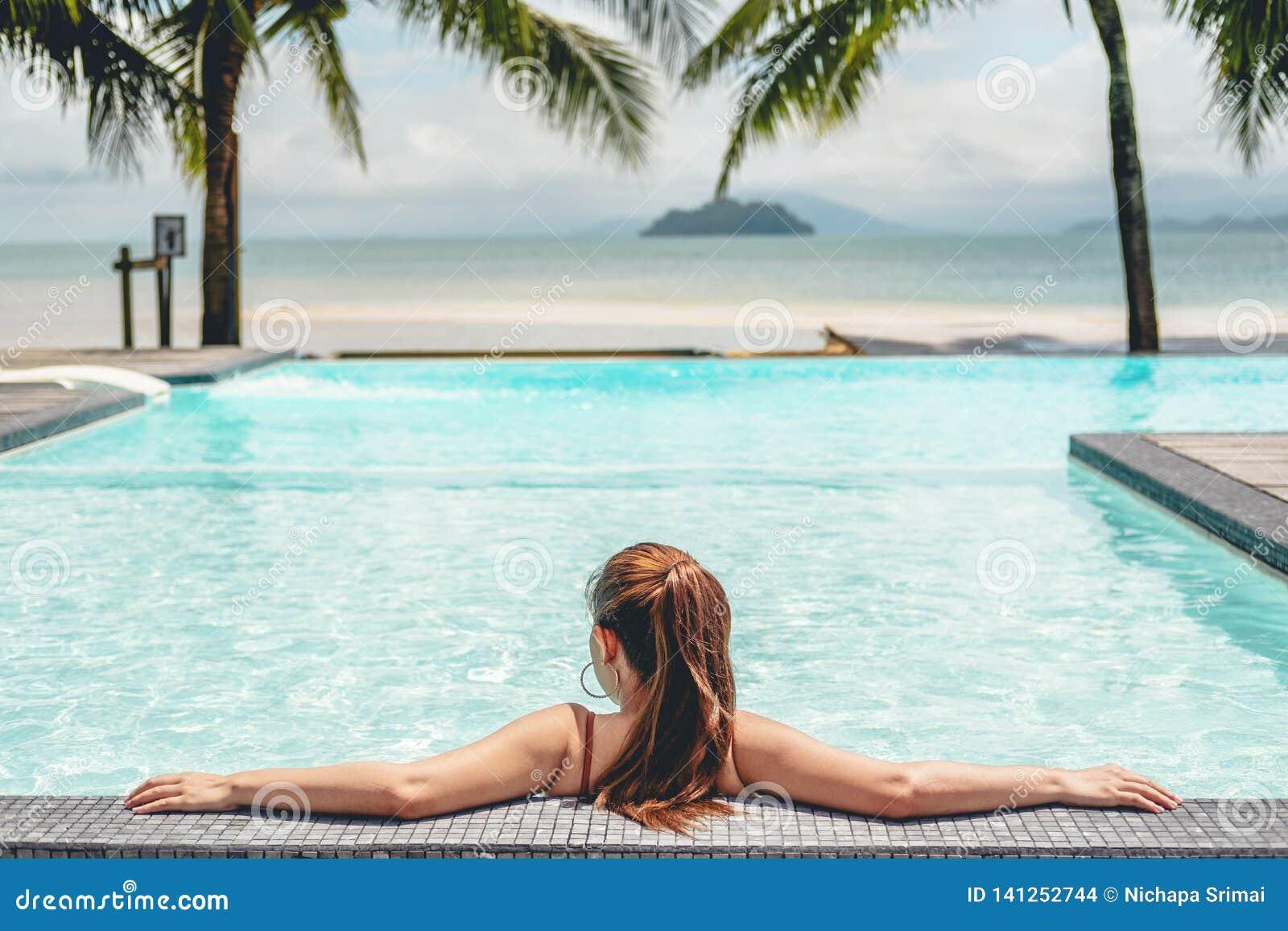 Relajación despreocupada de la mujer en concepto de las vacaciones de verano de la piscina