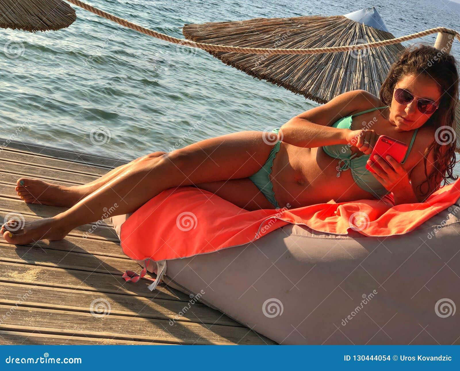 Relajación morena atractiva en la playa