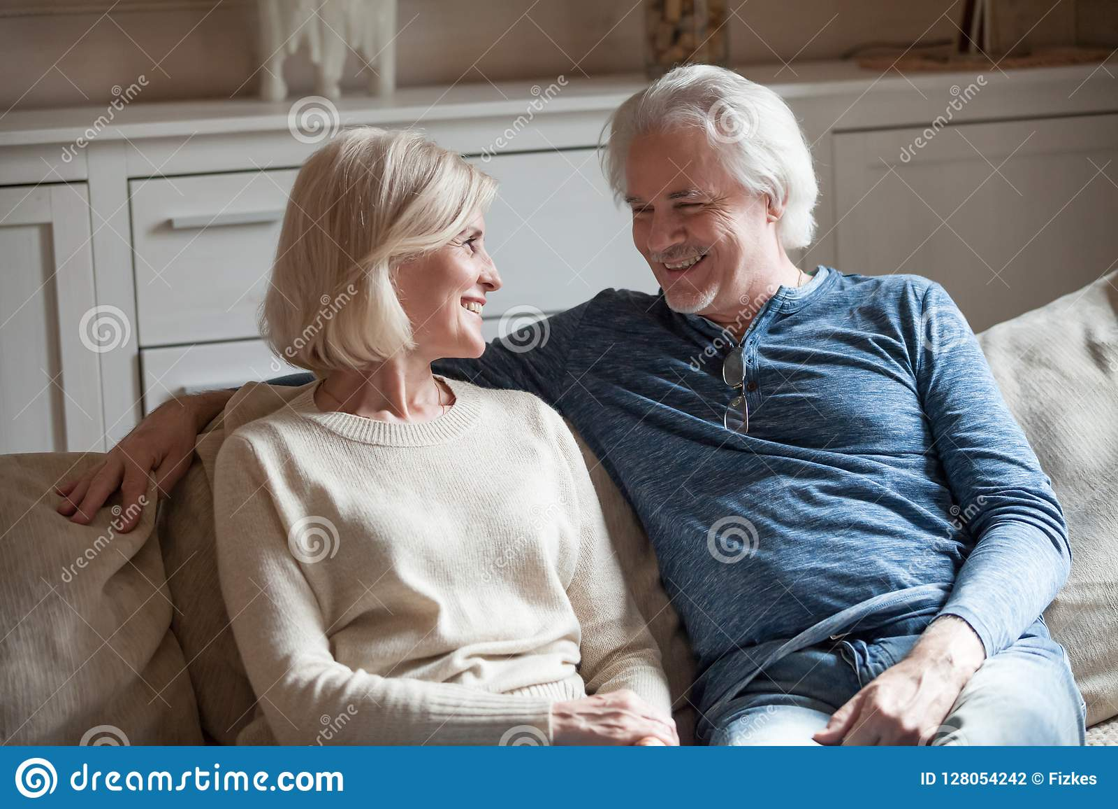 Relajación que habla de los pares mayores cariñosos felices en el sofá junto