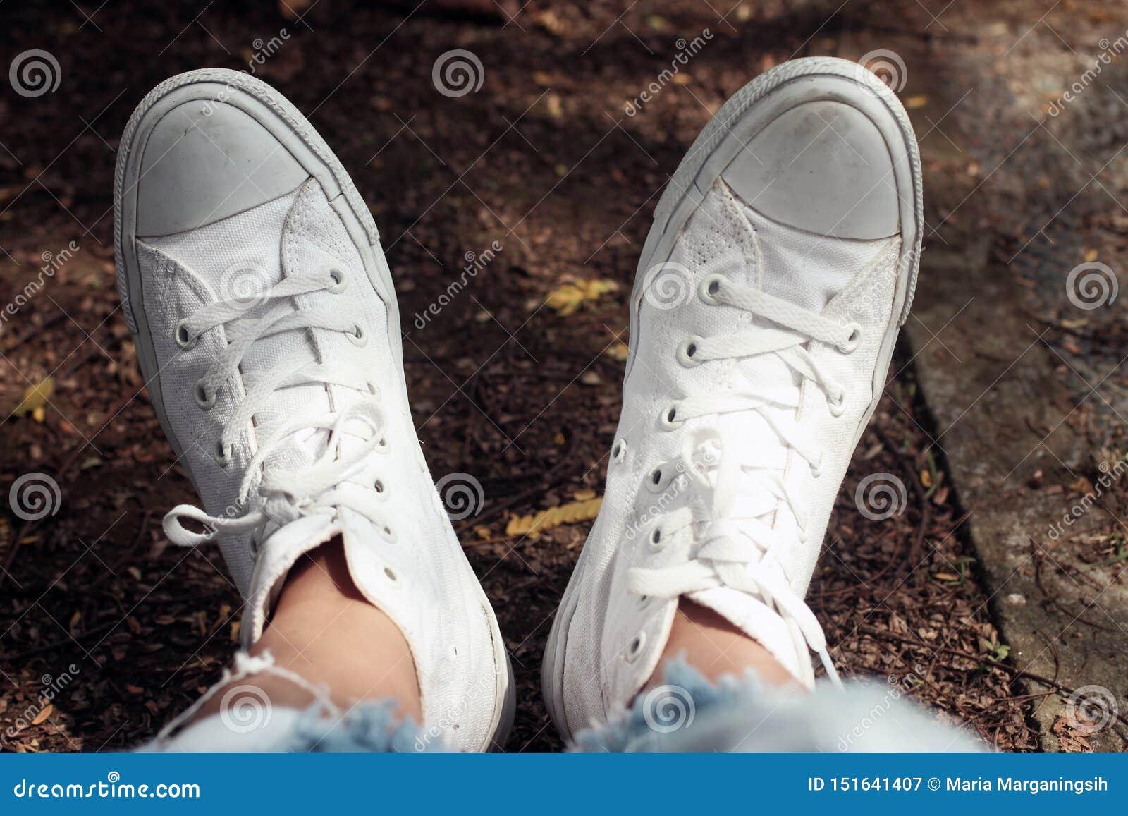 Relaksującego cieki młoda kobieta w białym sneakers tle Inspiracji pojęcie z kopii przestrzenią Ciało ludzkie część w przypadkowy