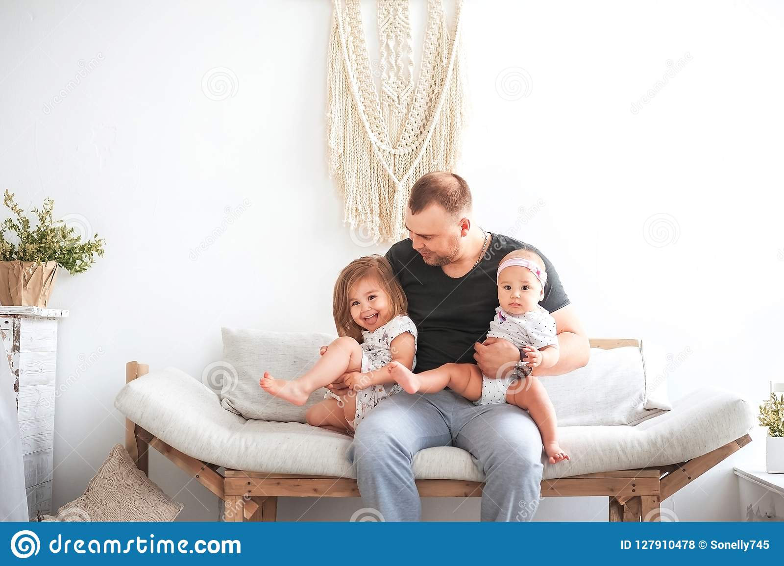 Kitchen in bright colors. Relationship in the family with young children and father. Dad hugs two daughters on the couch in the br