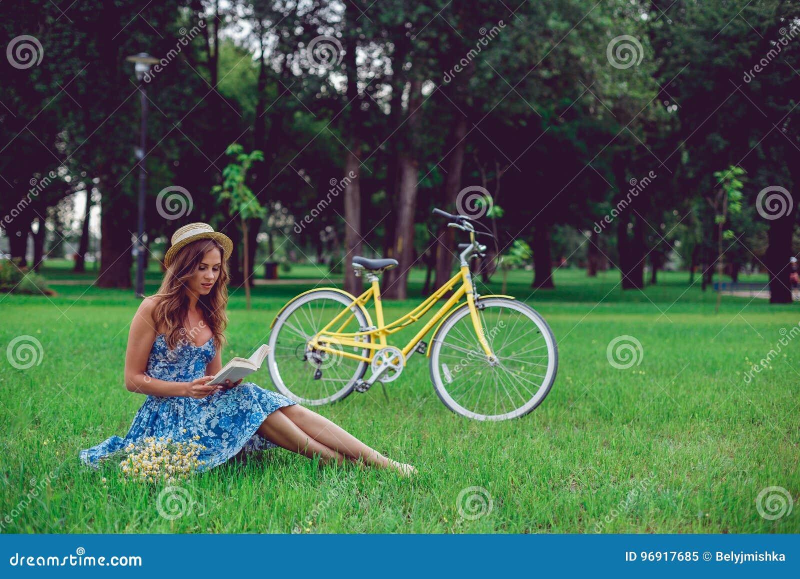 Relaxamento fêmea novo em uma grama verde com bicicleta em um parque em um dia ensolarado